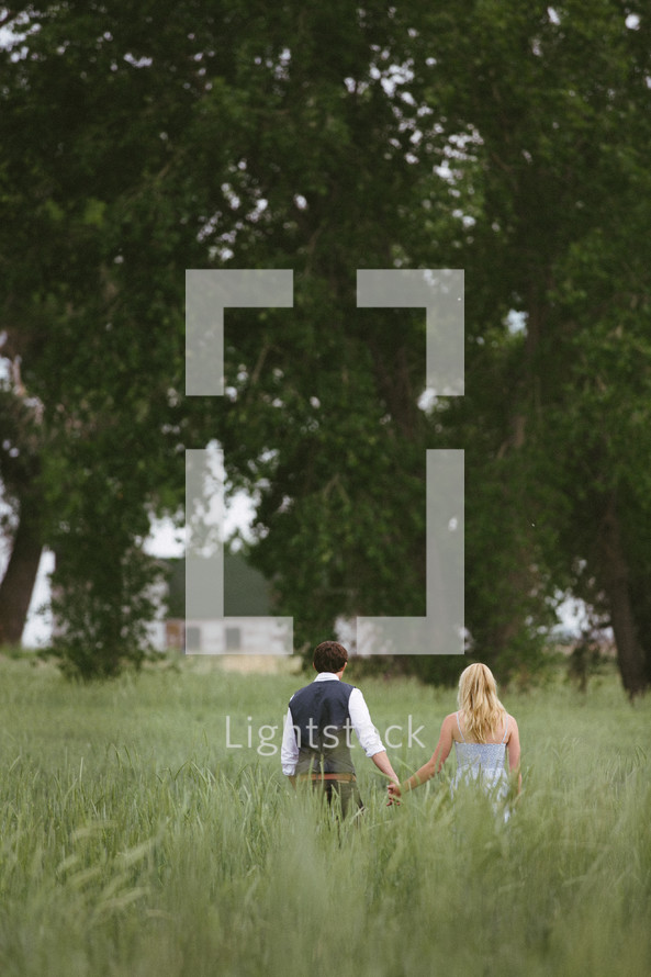 a couple holding hands and walking through a field
