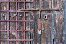 old wooden door with wrought iron bars. Old latch wrought iron.