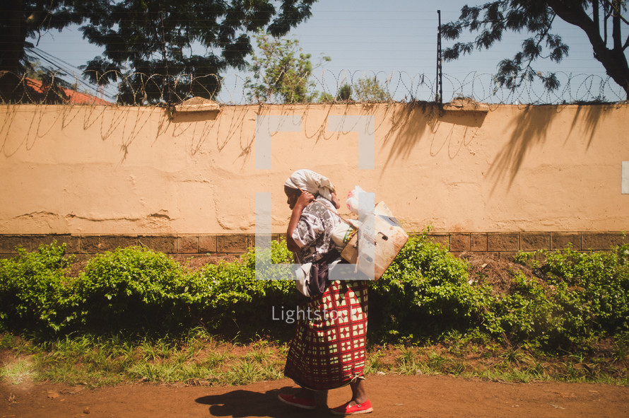 woman walking on a dirt road carrying bags