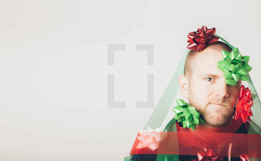 A man covered in Christmas bows and ribbon