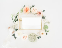 wreath of flowers around a glass box full of stationary