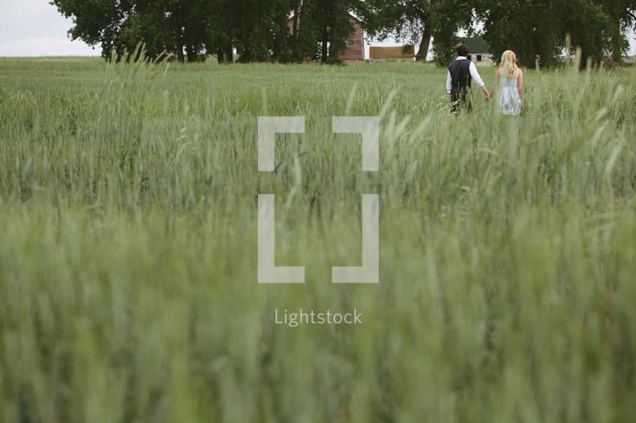 Couple walking in tall grass field