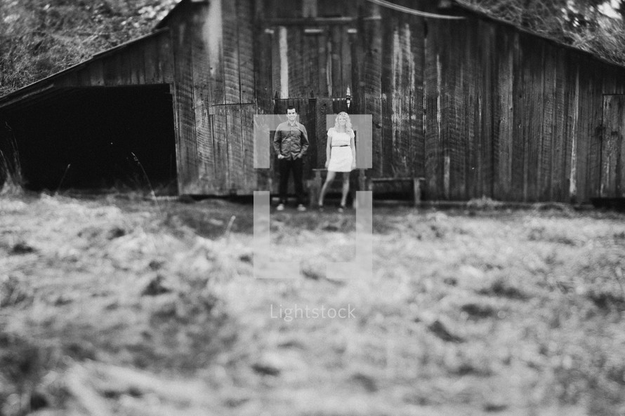 man and woman standing in front of a barn