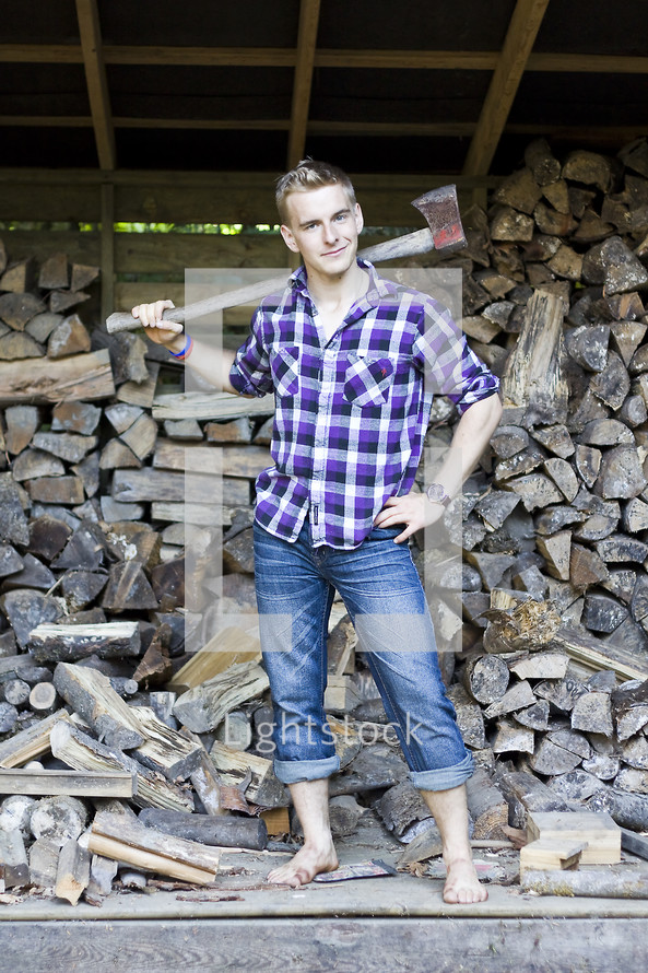 Man in rolled up denim jeans with axe over his shoulder standing in front of a wood pile.