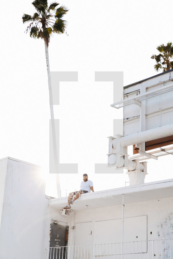 man sitting behind a billboard