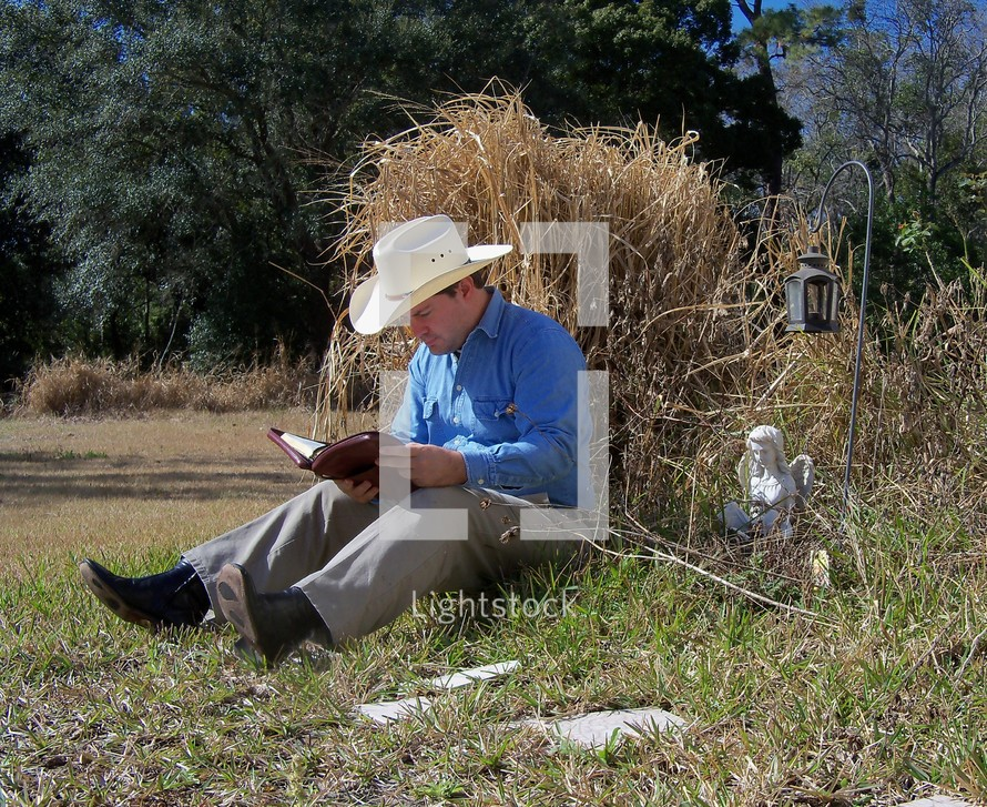 A man takes time from his chores in a rural country setting to study the word of God and read his bible, meditating on its truth and reflecting on the peace of God's promises. No matter how busy we get, we should and need to always stay in the word. It keeps us focused on our faith, the promises of God and the living truth of His word.