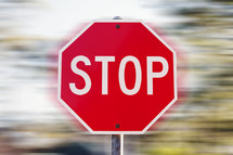 Stop sign against a fast-spinning background.