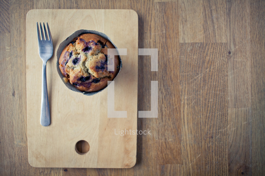 a fork and muffin on a wood plate