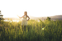 woman standing in tall grass in a sundress