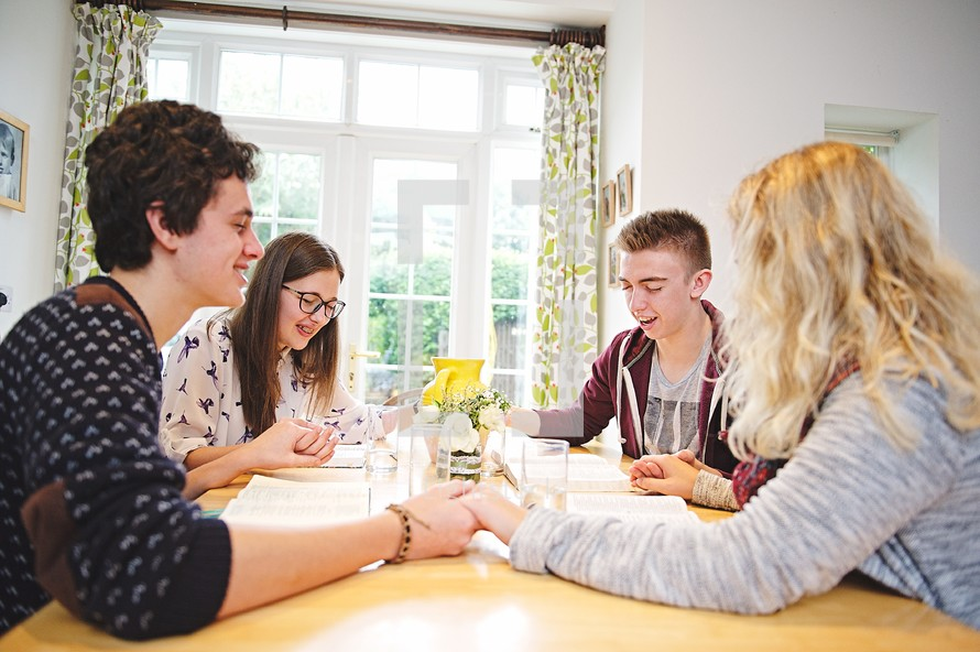 teens holdings hands in prayer at a Bible study