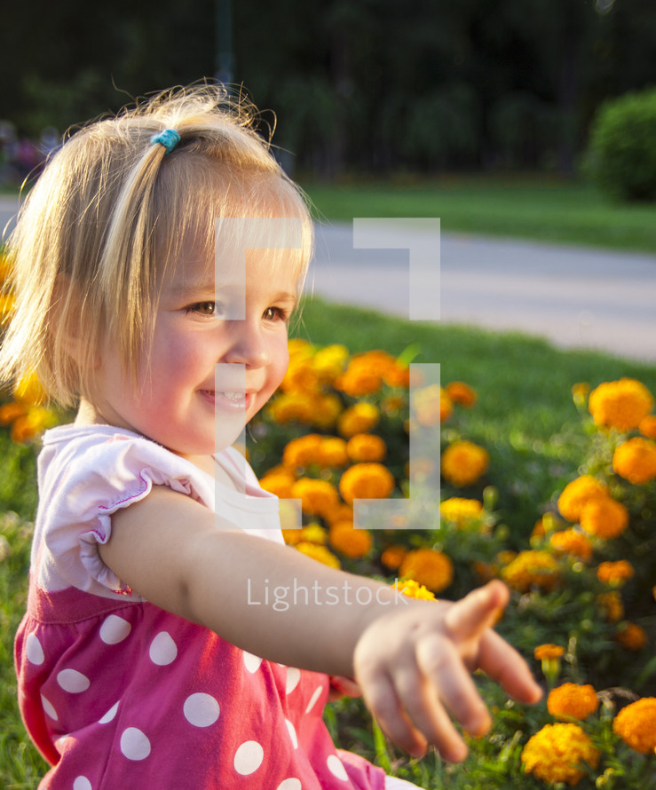 a girl child pointing to flowers