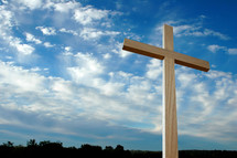 wood cross against a blue sky with clouds