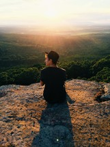 man sitting on a mountaintop at sunrise looking out