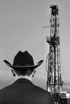 oilman standing in front of an oil rig