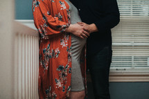 an expecting couple standing in a baby nursery