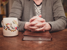 woman's praying hands over a Bible