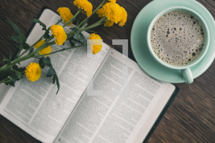 yellow flowers on the pages of a Bible and coffee cup