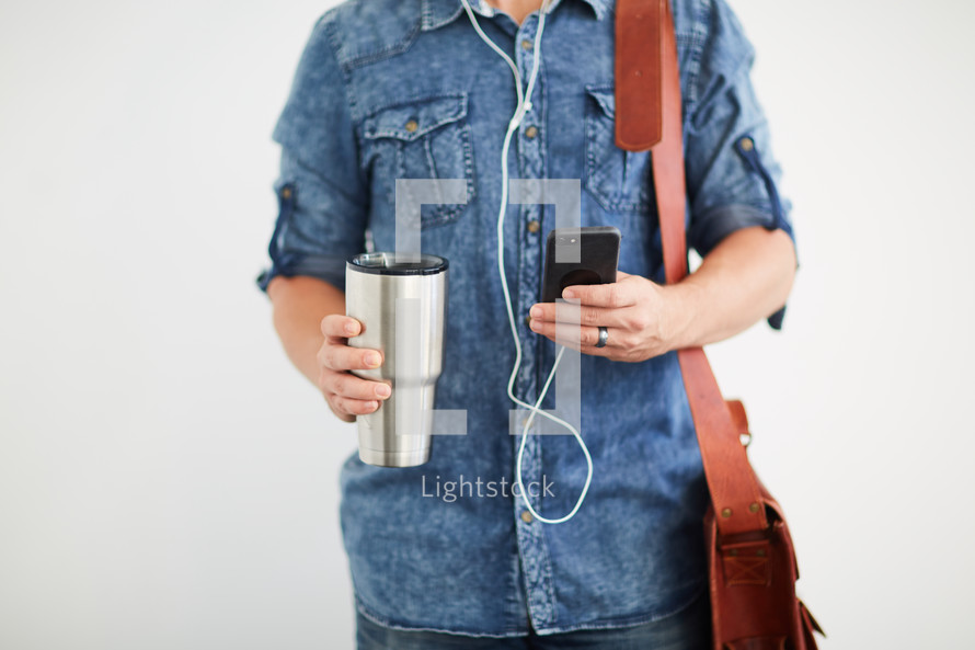 a man standing holding a messenger bag listening to earbuds