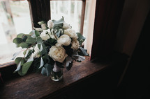 flowers in a vase in a window sill