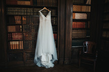 wedding gown hanging in a library