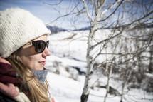 woman in wool cap standing outdoors in snow