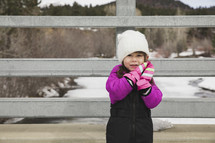 a little girl in a snowsuit and mittens