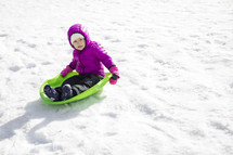 a child in a snowsuit playing outdoors