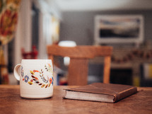 coffee mug and Bible on a wood table