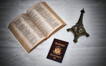 opened Bible, passport, and eiffel tower