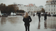 a woman walking outdoors on a rainy day