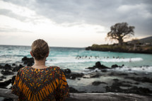 woman staring out at the water on an African Beach