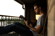 man playing a guitar on a balcony