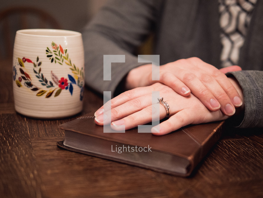 a woman with her hands on a Bible