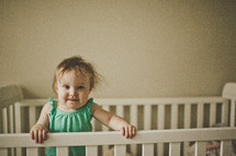 toddler girl in a crib