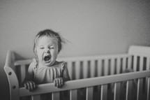 toddler yawning in a crib