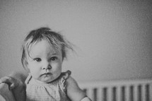 toddler girl in a crib