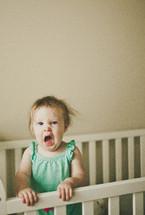 toddler girl yawning in a crib