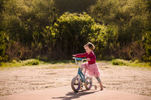 a toddler girl with a bicycle