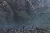 a couple climbing rocks to reach the top