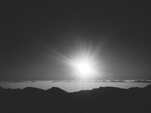 A glaring sun shines across clouds and mountaintops.