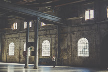 woman standing in an empty warehouse