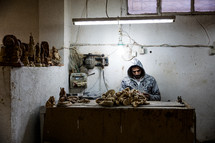 a man carving olive wood in the holy land