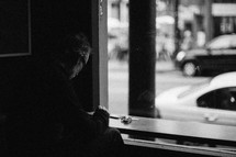 man sitting in a window seat in a cafe