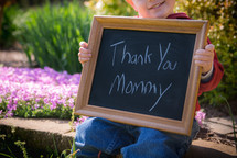 toddler boy holding a chalkboard sign that reads thank you mommy