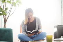 a woman sitting in a chair reading