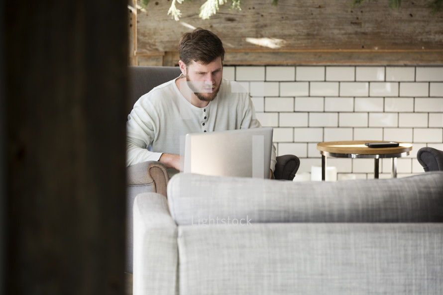 man sitting on a couch working on a laptop