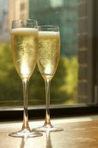 champagne glasses in a window sill