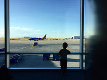 a boy looking out a window in an airport at airplanes on a runway