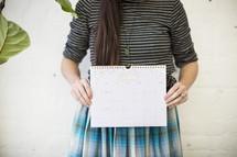 a woman holding up a calendar