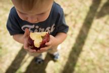 a toddler boy biting an apple